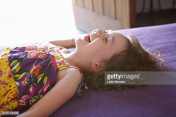Girl lying on bed laughing