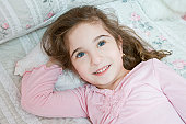 Girl (4-5) lying on bed, looking away, high angle view