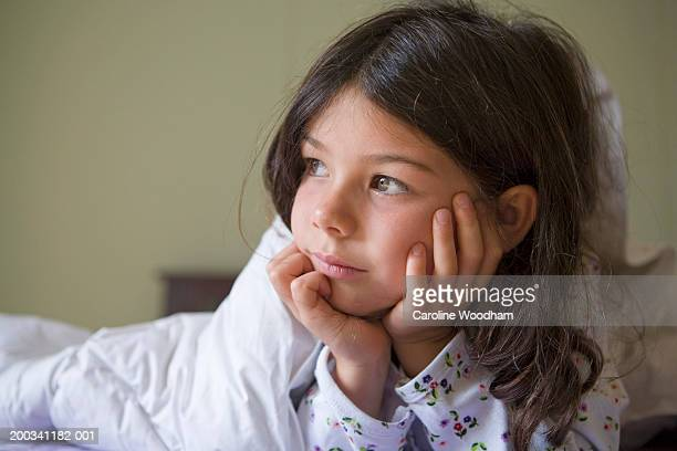 Girl (4-6) lying on bed, resting chin on hands, looking away
