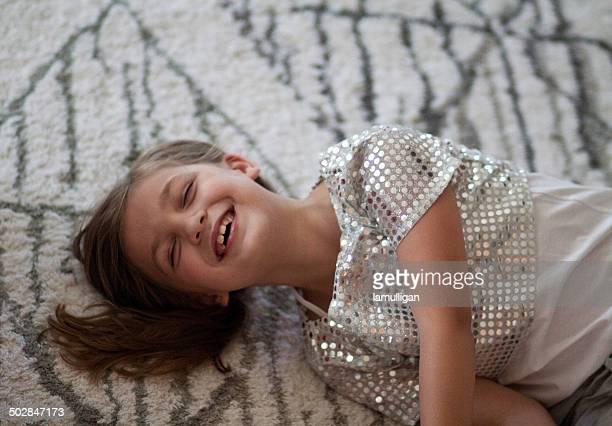 Girl (6-7) lying on carpet