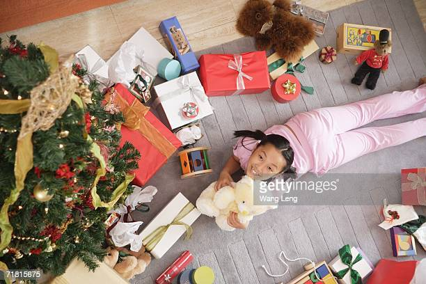 Girl lying on floor, surrounded by presents, holding teddy bear, looking at camera