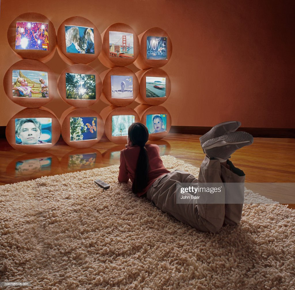 Girl (10-12) lying on floor, watching different TV screens : Stock Photo