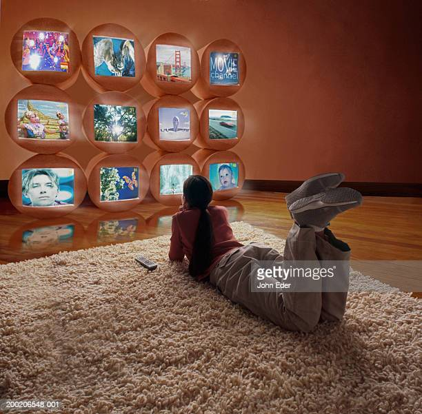 Girl (10-12) lying on floor, watching different TV screens