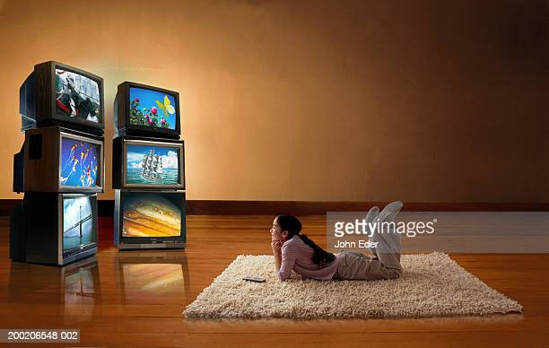 Girl (10-12) lying on floor, watching TV screens