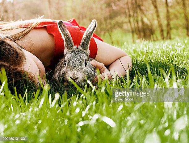 Girl (10-12) lying on grass, holding rabbit, ground view