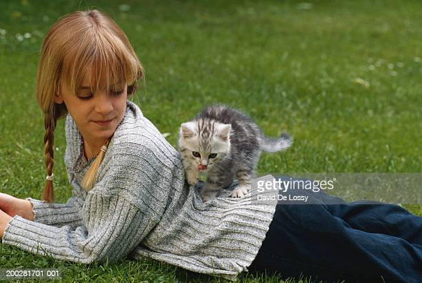 Girl (6-7) lying on grass with cat on back