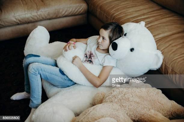 Girl lying on her  large Polar teddy bear