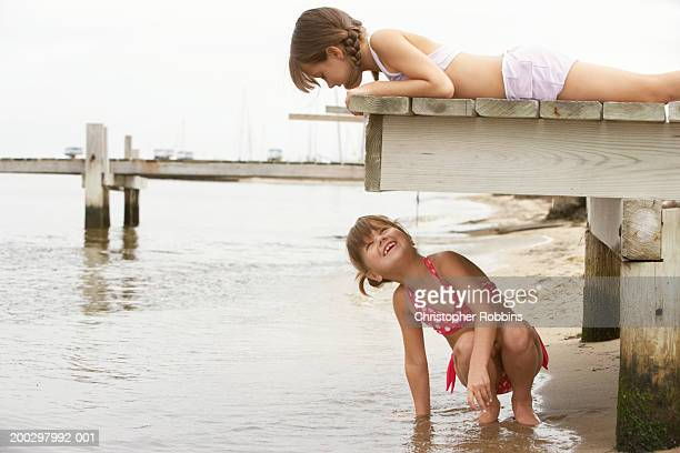 Girl (8-10) lying on jetty, looking at girl (5-7) crouching underneath