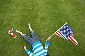 Girl (3-5 years) lying on lawn, waving USA flag, elevated view