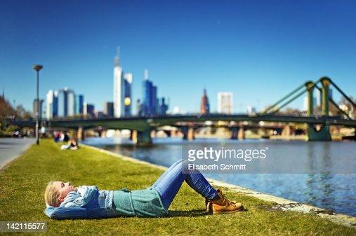 Girl lying on riverbank : Stock Photo