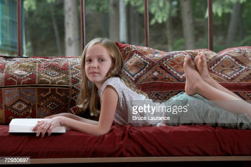 Girl (8-9) lying on sofa, holding book, portrait