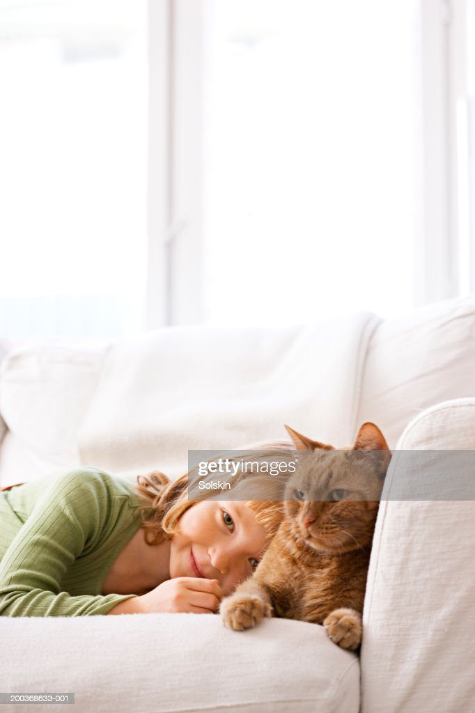 Girl (4-6) lying on sofa with cat, smiling, portrait, close-up : Stock Photo