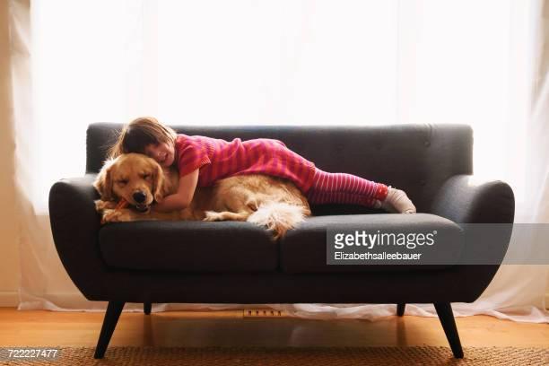Girl lying on sofa with her golden retriever dog