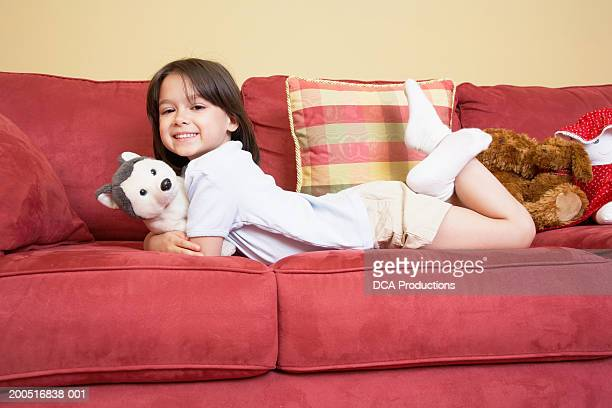Girl (5-7) lying on sofa with stuffed animals, portrait