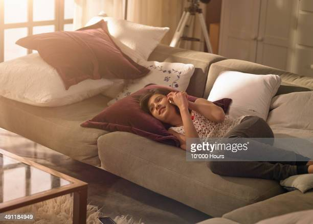 A girl lying on the sofa talking on her phone
