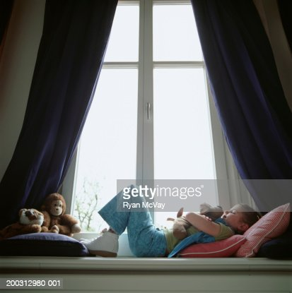Girl (6-7) lying on window sill, hugging toy dog : Foto stock