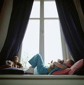 Girl (6-7) lying on window sill, hugging toy dog