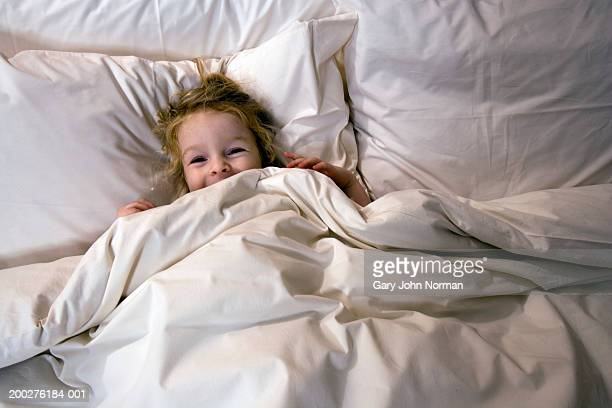 Girl (3-5) lying under covers, laughing