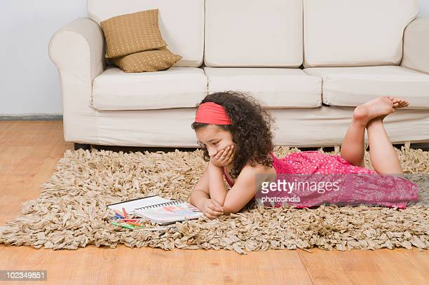 Girl lying with a notebook and colored pencils