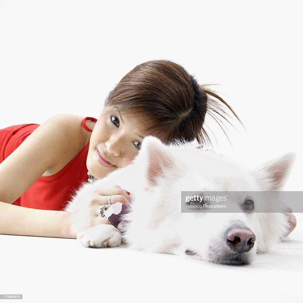 Girl lying with dog indoors : Stock Photo
