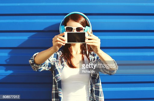 Girl makes self-portrait on smartphone listens music, screen phone : Bildbanksbilder