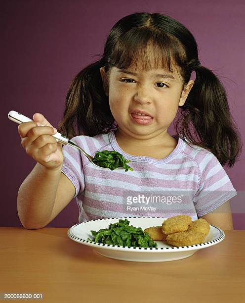 Girl (5-7) making a face at fork full of spinach, portrait