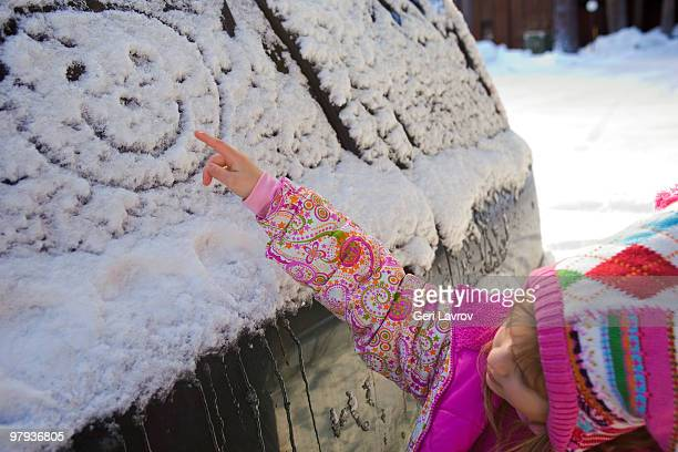 Girl making a happy face shape on a car with snow