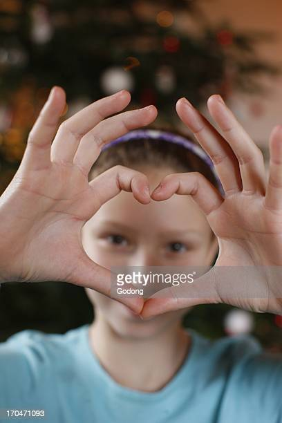 Girl making a heart shape with her fingers France
