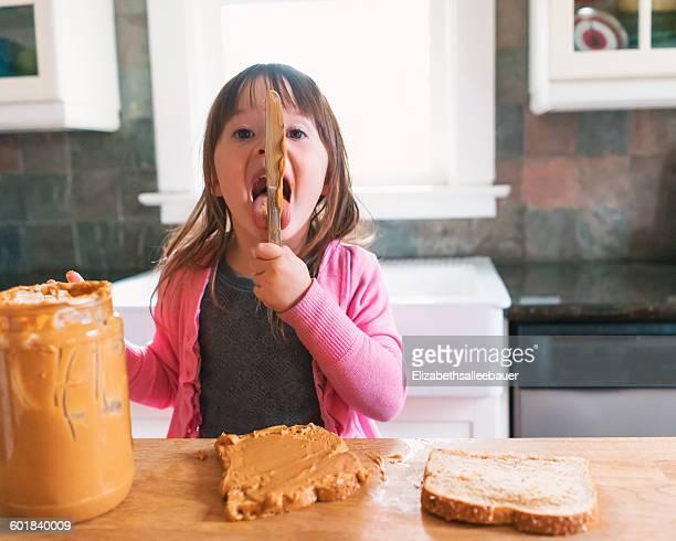 Girl making a peanut butter sandwich, licking the knife