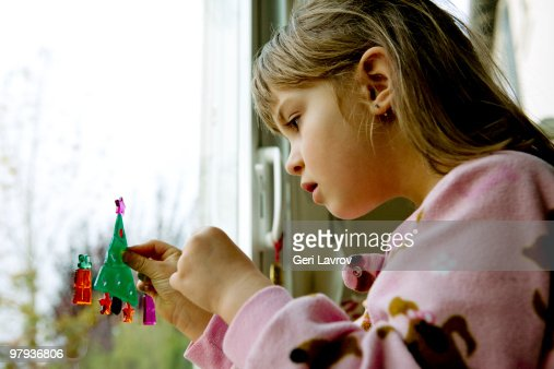 Girl making a toy Christmas tree on patio door : Stock Photo