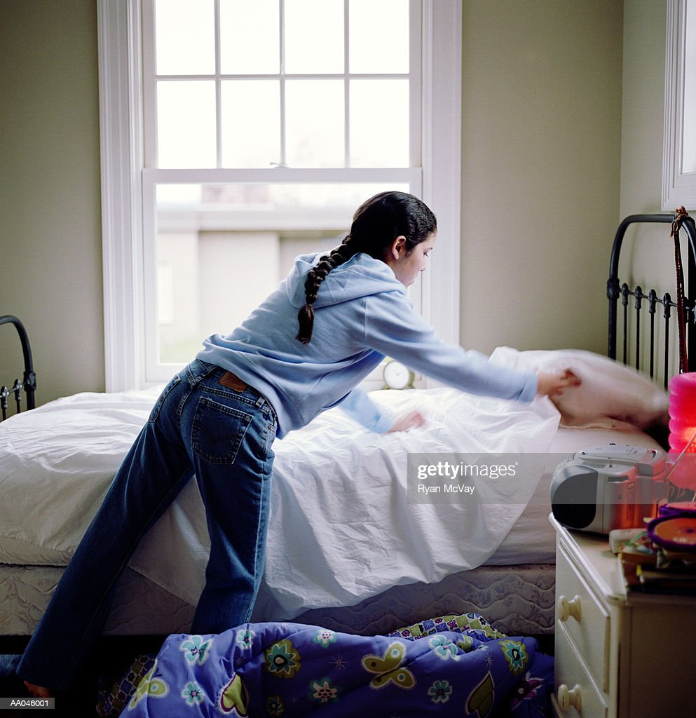 Girl (10-12) making bed, rear view