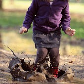 Girl making big muddy splash with joy.