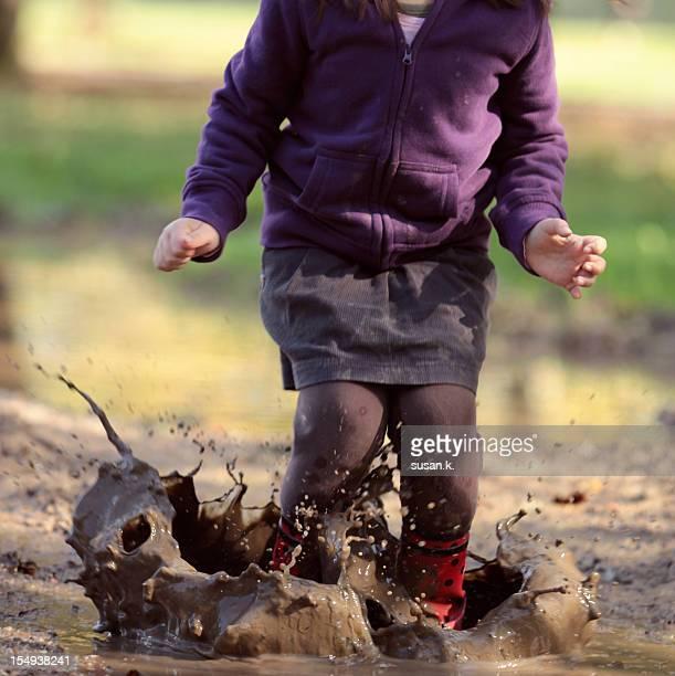 Girl making big muddy splash with joy.