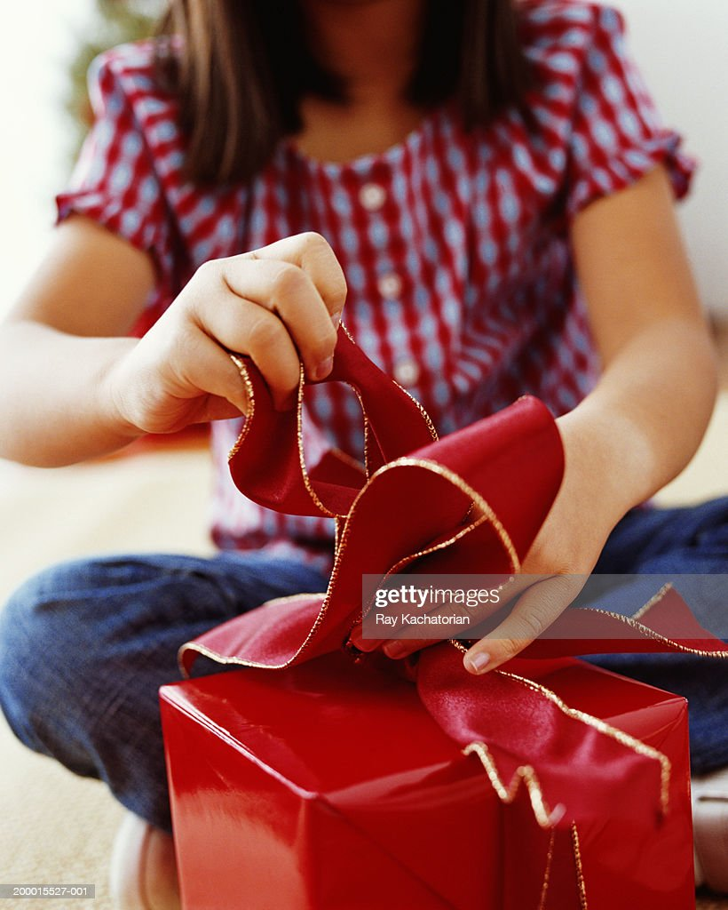 Girl (5-7) making bow for present : Stock Photo