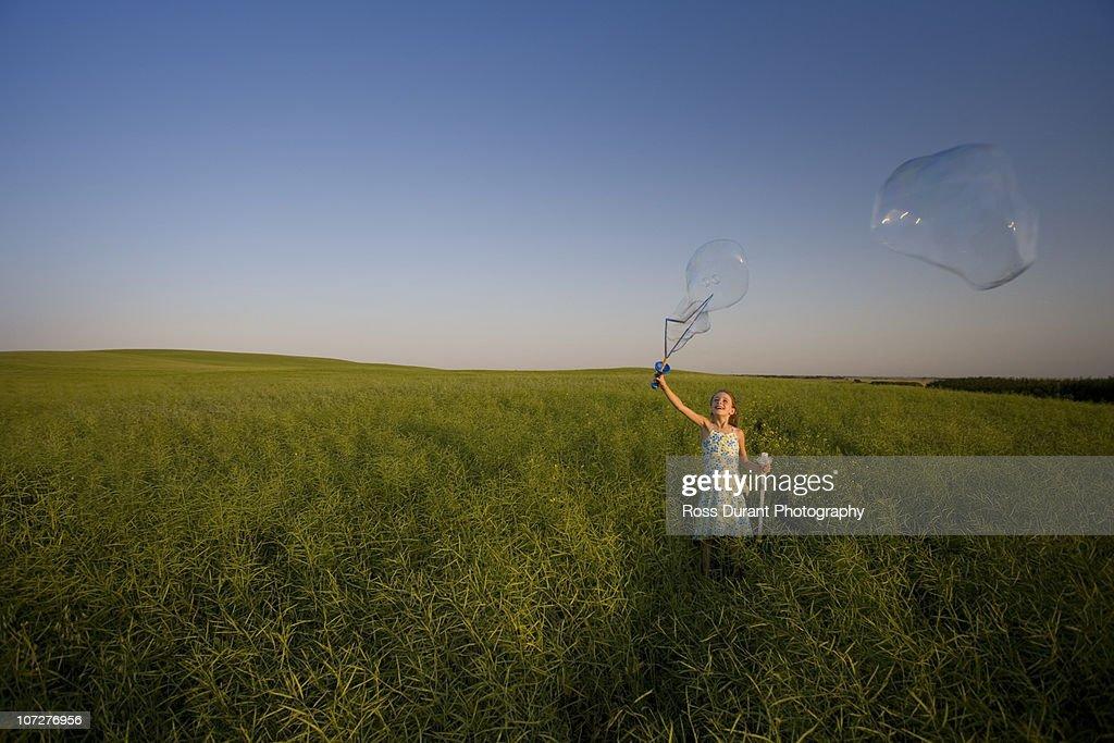 Girl making bubbles in field : Stock Photo