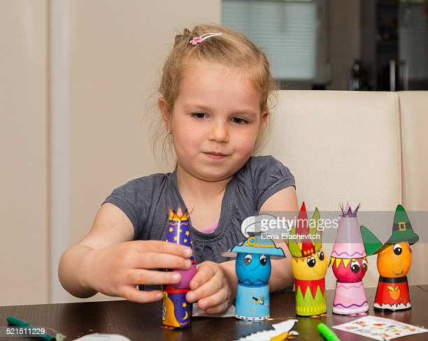 Girl making colorful Easter eggs