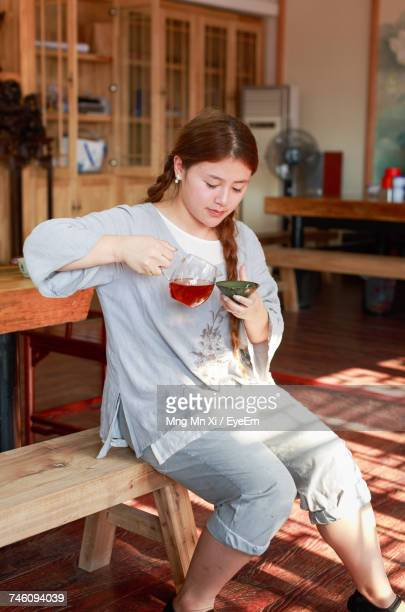 Girl Making Drink While Sitting On Wooden Table At Home