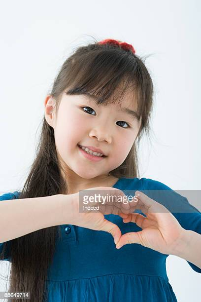Girl making heart shape with hands, smiling