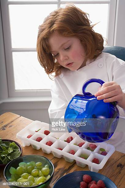 Girl (6-7) making ice cubes in kitchen