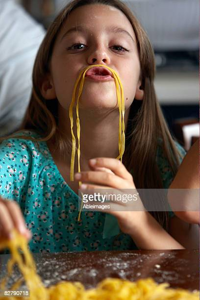 girl making moustache with spagetti