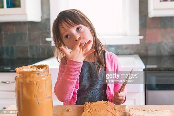 Girl making peanut butter sandwich, licking fingers