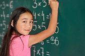 Girl making some exercises on the blackboard