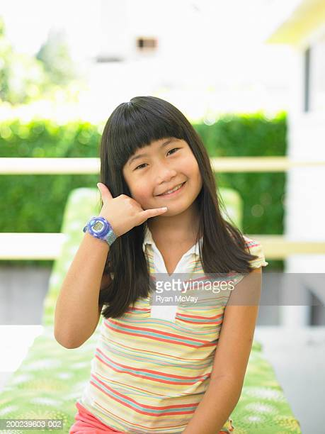 Girl (8-10) making telephone gesture, smiling, portrait