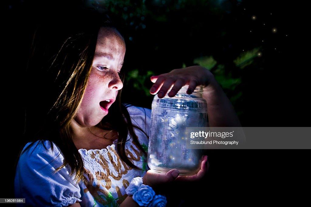 Girl marvels at jar full of fireflies : Stock Photo