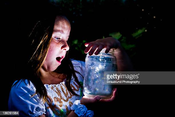 Girl marvels at jar full of fireflies