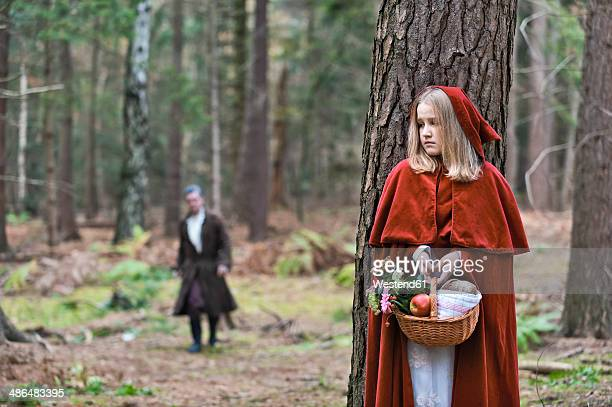 Girl masquerade as Red Riding Hood hiding behind a tree in the wood