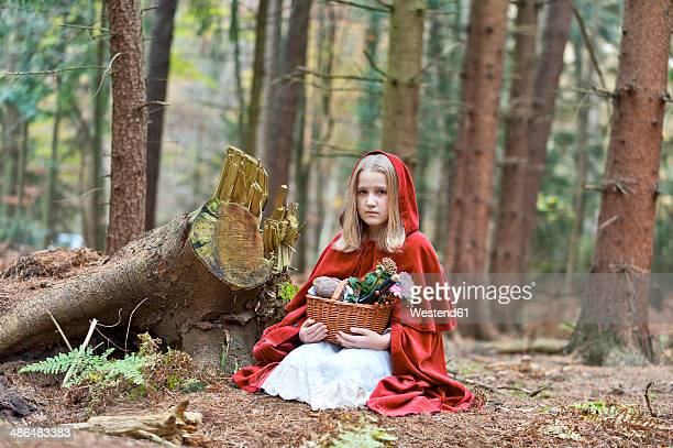 Girl masquerade as Red Riding Hood sitting on the ground in the wood
