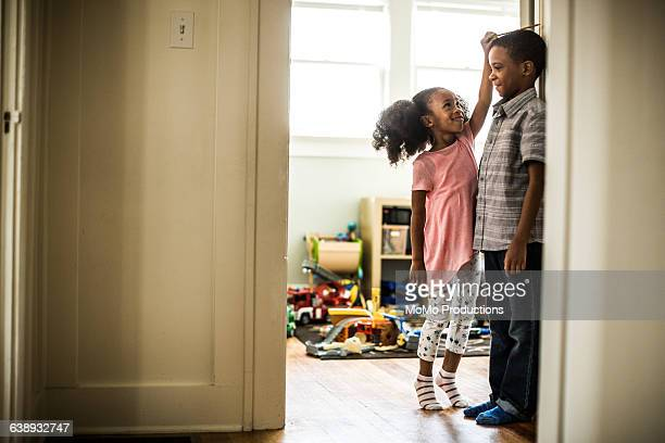 girl measuring brothers height