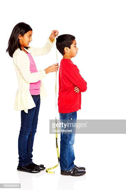 Girl measuring height of her young brother