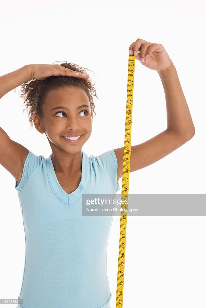 Girl measuring height : Stock Photo